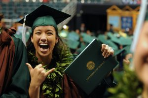 A happy UH graduate with her degree.