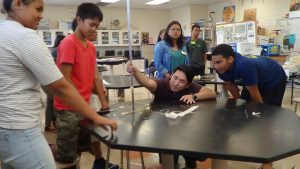 Dr. John Hirano, (center) a Ph.D. in engineering, works with incoming Waipahu High freshmen in the first Early College STEM summer camp.