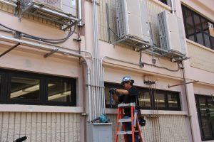 A worker at Campbell High School installs energy-efficient air conditioning.