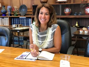 New DOE superintendent Dr. Christina Kishimoto smiles while writing in book