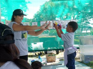 'OHANA NUI IN ACTION: Jessica Reyes, a Partners in Development mobile preschool staff member, counts with Relmersan, who was with his family at the Kaka'ako Family Assessment Center. The preschool program gives children a positive start.