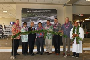 Airlines Committee of Hawaii Co-Chair Blaine Miyasato (from left to right), House Vice Speaker Mark Nakashima, Governor David Ige, HDOT Director Jade Butay, Senate President Ronald Kouchi, Hawaiian Airlines President & CEO Peter Ingram, Hensel Phelps Vice President Thomas Diersbock, and Kahu Kordell Kekoa participate in the untying of the maile lei during the groundbreaking ceremony for the Mauka Concourse project.