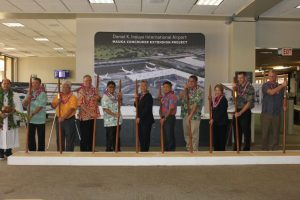 Kahu Kordell Kekoa (from left to right), HDOT Airport Division Deputy Director Ross Higashi, Rep. Richard Onishi, Airlines Committee of Hawaii Co-Chair Blaine Miyasato, House Vice Speaker Mark Nakashima, Governor David Ige, HDOT Director Jade Butay, Senate President Ronald Kouchi, Sen. Lorraine Inouye, Hawaiian Airlines President & CEO Peter Ingram, Hensel Phelps Vice President Thomas Diersbock participate in the turning of the soil with O'o sticks.