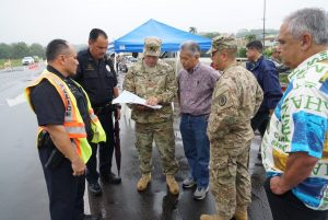 Hawai'i National Guard and police officers discuss emergency strategies with the governor.