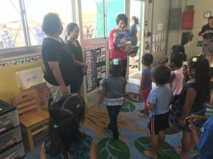 First lady Dawn Amano Ige reads to children at the blessing of Kahauike Village's new preschool.