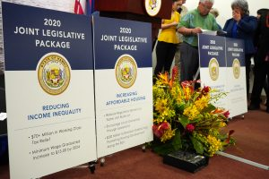 Signs at a news conference highlight the Joint Legislative Package of bills.