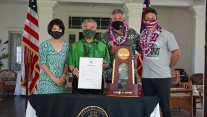 Governor Ige and the First Lady, coach Charlie Wade and team captain Colton Cowell with the NCAA trophy and proclamation.